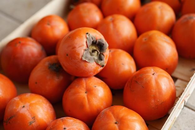Спелая оранжевая хурма в ящике с текстурой фона из фруктов хурмы