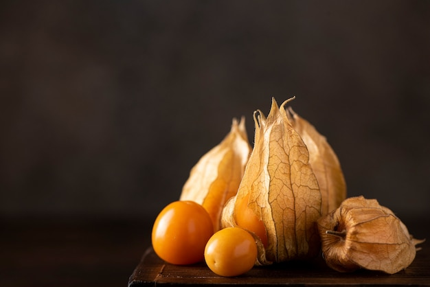 Ripe orange physalis berries on a wooden board, close-up