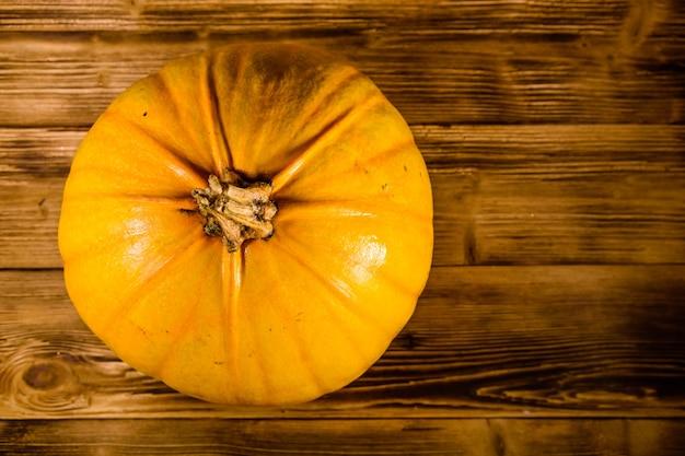 素朴な木製のテーブルに熟したオレンジ色のカボチャ。上面図