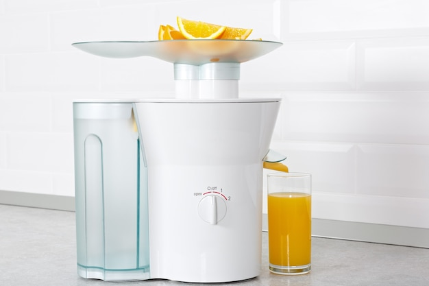 Дольки спелого апельсина в соковыжималке и стакан фреша на кухне.
