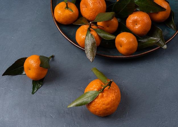 Спелый оранжевый мандарин в тарелке на сером фоне макроса