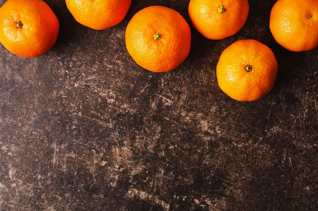 Ripe orange tangerine lies on a dark marble table with scratches. juicy fruit.