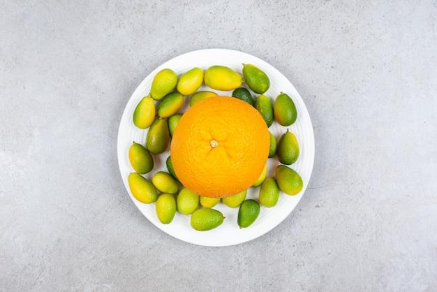 Ripe orange with pile of kumquats on white plate.