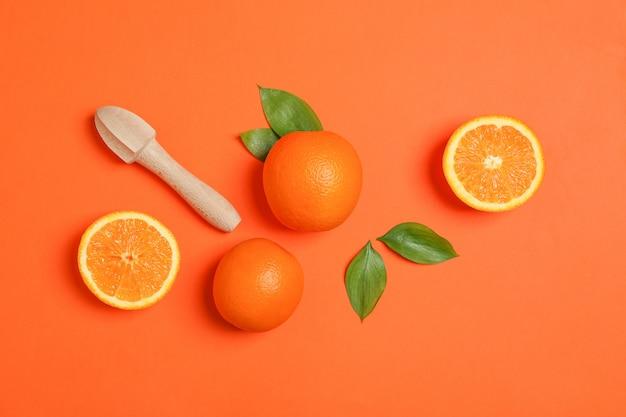 Спелые апельсины, листья и деревянные соковыжималки на цвет фона. вид сверху спелые апельсины, листья и деревянные соковыжималки на цвет фона. вид сверху