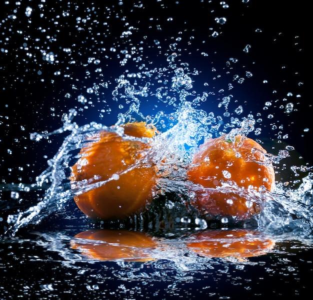 Ripe oranges with water splash