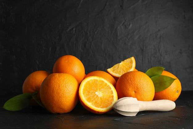 Спелые апельсины с деревянной соковыжималкой на черном столе на темном фоне, место для текста