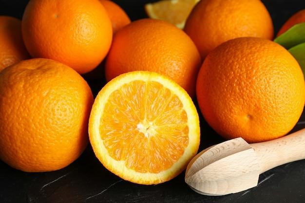 Спелые апельсины с деревянной соковыжималкой на черном столе, крупным планом