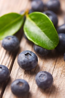 Ripe organic blueberries close-up on a wooden background with leaves. selective focus