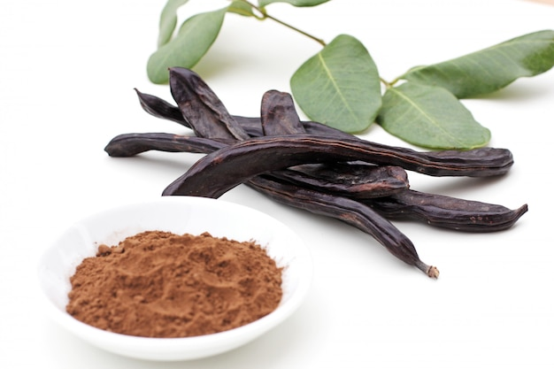 Ripe organic carob fruit pods with green leaves from locust tree and carob powder