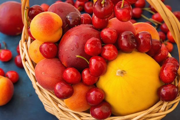 Ripe organic fruits sweet cherries nectarines apricots melon in wicker basket