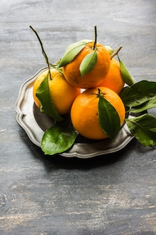 Ripe organic oranges on dark wood