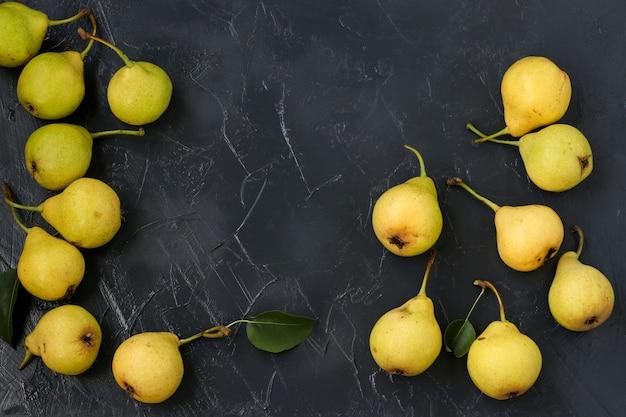 熟した有機梨は、暗い背景に任意の順序で配置されています、上面図、コピースペース