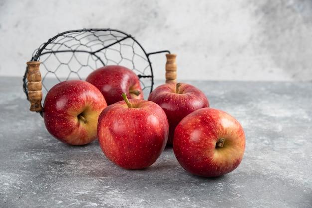 Спелые органические красные яблоки из металлической корзины на мраморном столе.