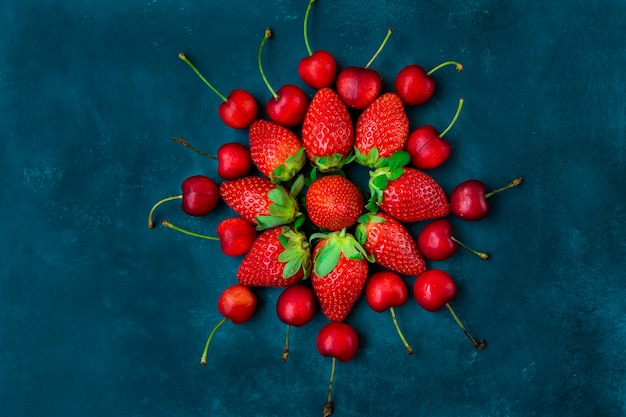 熟した有機イチゴ、花、青い背景の形に配置された光沢のある甘いチェリー