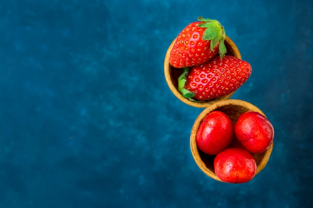 ワッフルアイスクリームコーンの熟した有機イチゴの光沢のある甘いチェリー。濃い青の背景