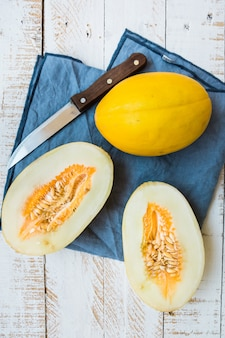 Ripe organic yellow melons, halved and whole on white plank wood garden table