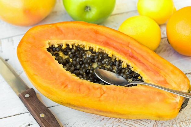 Ripe papaya cut in half spoon knife, citrus fruits on plank wood table, top view