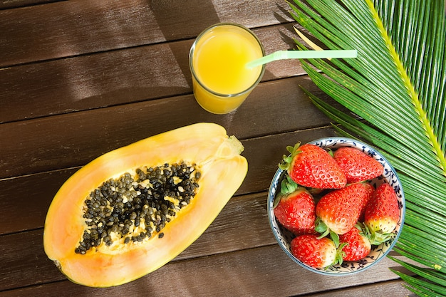 Ripe papaya fresh strawberries in bowl pineapple citrus juice