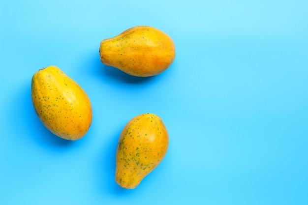青の背景に熟したパパイヤの果実。コピースペース