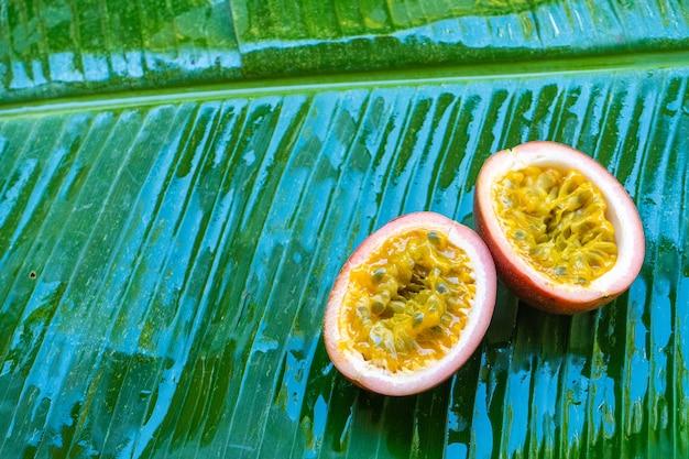 濡れたバナナの葉の上に、熟したパッションフルーツ。ビタミン、果物、健康食品。