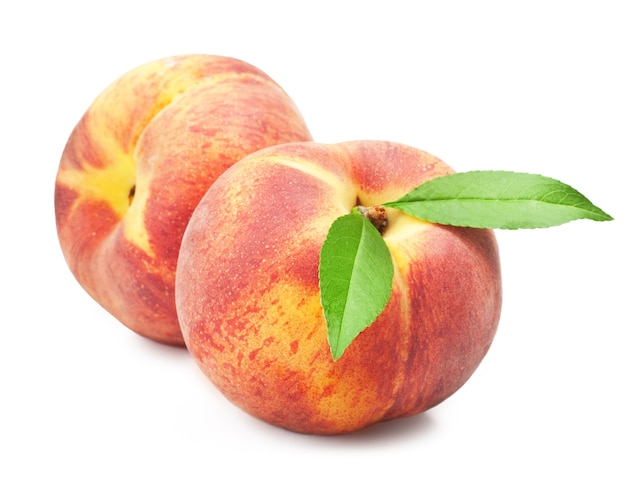 Ripe peach fruit with leaves on white surface