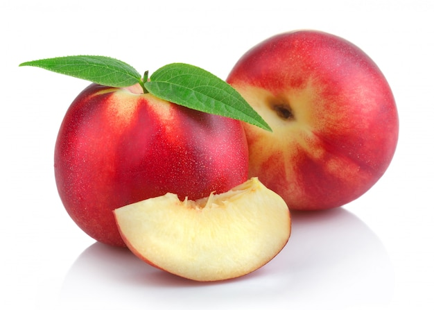 Ripe peach (nectarine) fruits with slices isolated