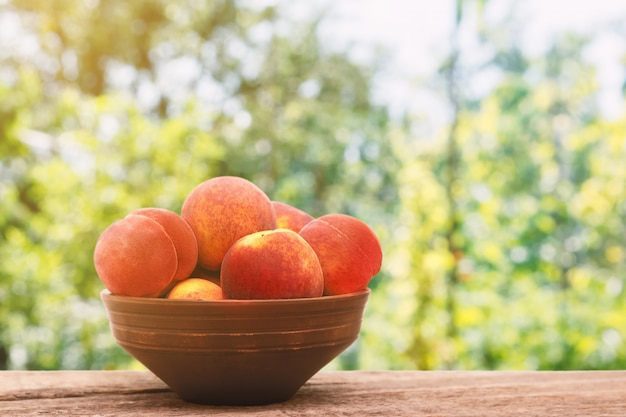 Ripe peaches in a bowl on wooden background.
