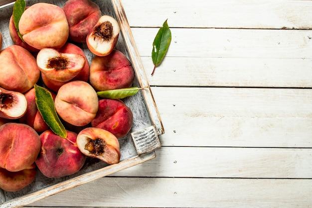 箱に入った熟した桃。白い木製のテーブルの上。