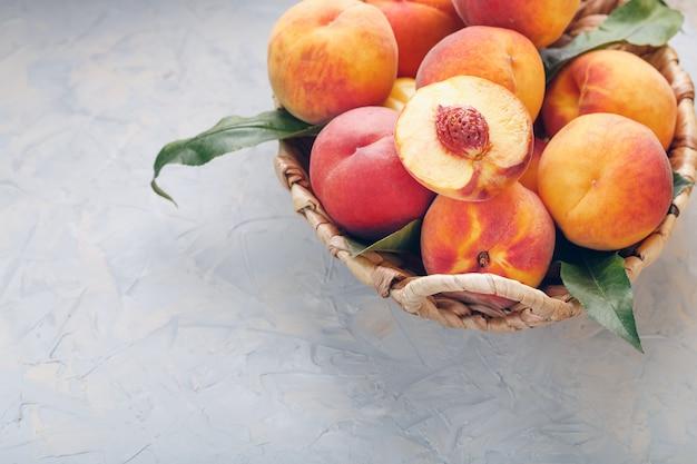 ジューシーなピーチスライスと石のピットで、灰色の石のテーブルに籐のバスケットで熟した桃。