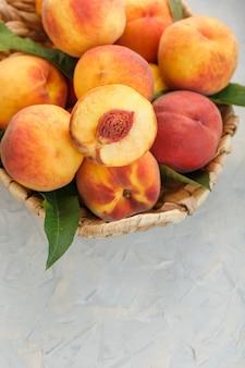 ジューシーなピーチとストーングレーのテーブルに籐のかごで熟した桃
