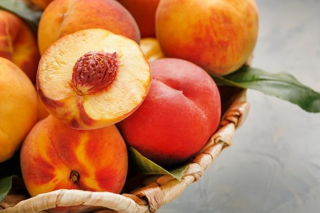 灰色の石のテーブルに籐のかごで熟した桃