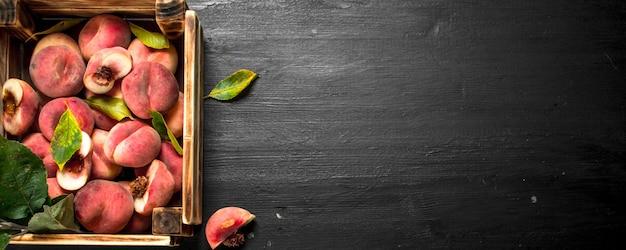 Спелые персики в деревянном ящике. на черной доске.
