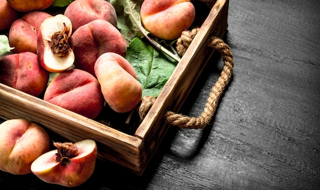 Спелые персики в деревянной коробке на черной доске