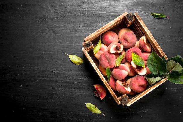 木箱に熟した桃。黒い黒板に。