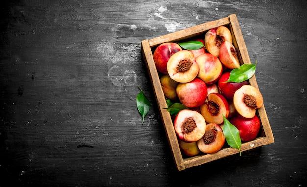Спелые персики в старой коробке.