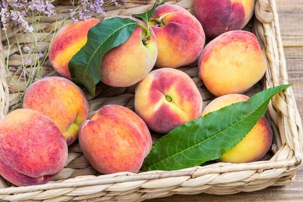 Спелые персики в плетеной корзине. деревянный фон. плоская планировка