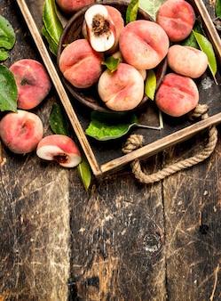 Спелые персики на подносе. на деревянном фоне.