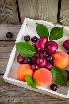 Спелые персики, сливы и вишня в коробке