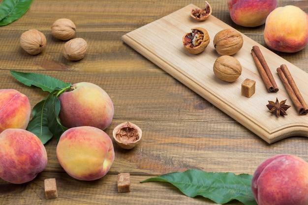 テーブルの上に緑の葉を持つ熟した桃。クルミ、シナモンスティック、スターアニスが乗っています。木製の背景。上面図