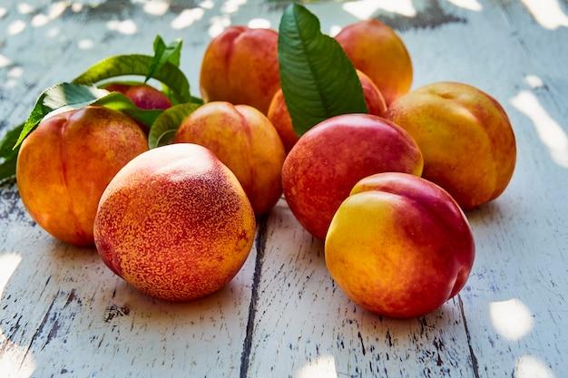古い木製のテーブルの上の葉を持つ熟した桃