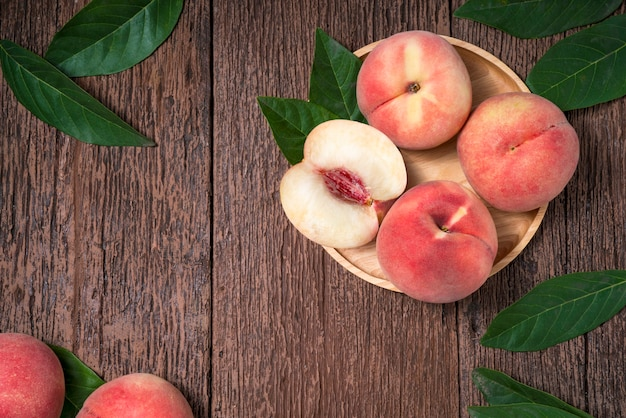 古い木製のテーブルの上の葉で熟した桃。木製の背景で新鮮な韓国桃の木の板。