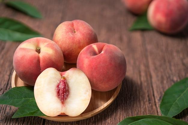古い木製のテーブルの上の葉を持つ熟した桃。木製のテーブルで新鮮な韓国桃の木の板。