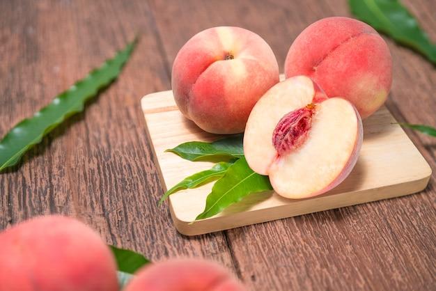 古い木製のテーブルの上の葉で熟した桃。