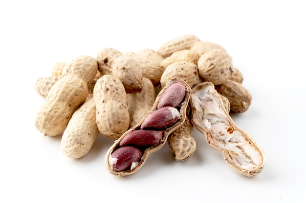 Ripe peanuts, peeled and seen inside on a white background.