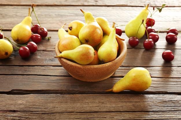 熟した梨とさくらんぼの木製のテーブルをクローズ アップ