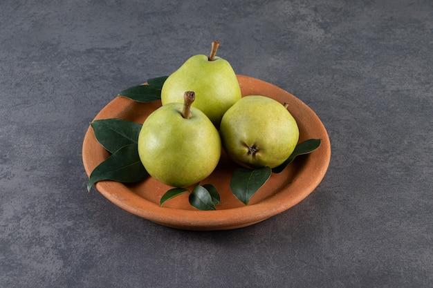 大理石の表面のプレートに熟した梨