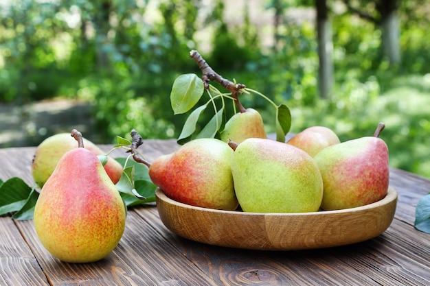 Спелые груши на деревянном столе в саду