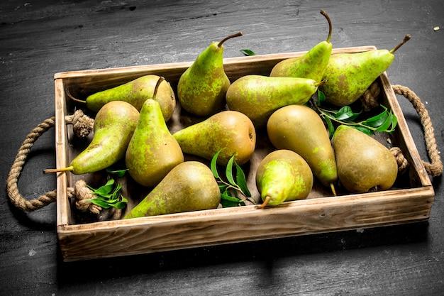 Ripe pears onn old tray on black chalkboard.