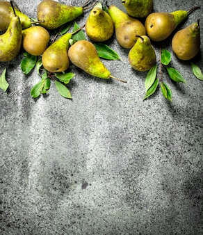 Ripe pears with leaves on rustic table.
