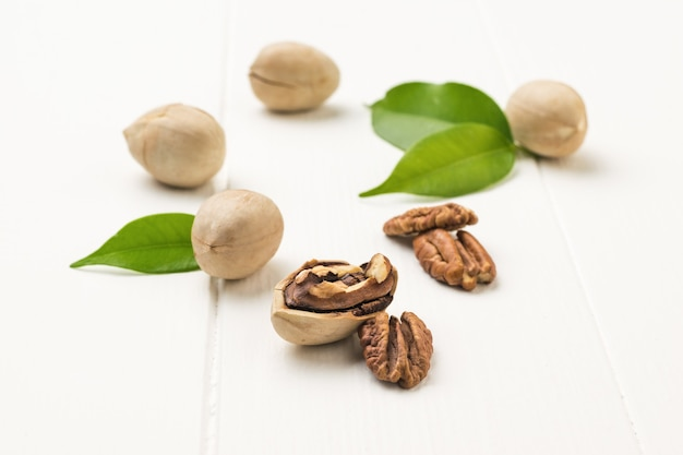 Ripe pecans in a light shell on a white wooden table